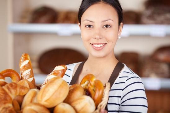 smiling salesgirl working in bakery